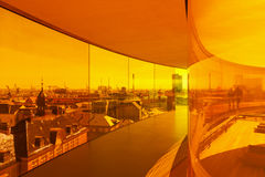 View over Aarhus from inside the installation on top of Aarhus a. Aarhus, Denmark - May 2, 2017: View through orange tinted glass over Aarhus from inside Olafur Royalty Free Stock Image