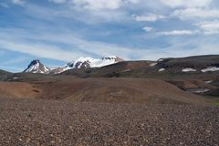 View over barren dry brown hilly rough terrain on snow capped mountains - Iceland royalty free stock image