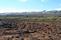 View over barren rocky plain on mountain range with spots of snow, Iceland royalty free stock photo