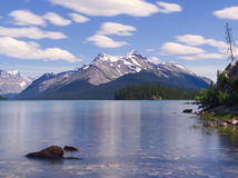 View Over Beautiful Blue Maligne Lake on a Summers Day. Clear Blue Maligne Lake with Snowcapped Mountains in the Background on a Sunny Day Stock Photos
