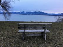 View over a bench and lake to mountains Stock Photography