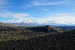 View over a black volcanic lava landscape from the Inferno Cone. Northward view from the Inferno Cone. A cinder cone rising above a landscape of black volcanic stock photography