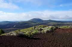 View over a black volcanic lava landscape from the Inferno Cone. Westward view from the Inferno Cone. A cinder cone rising above a landscape of black volcanic Royalty Free Stock Photo