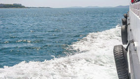 View over the boats deck. Side view, over the deck of the saling boat on the blue sea with water waves on the side Royalty Free Stock Images