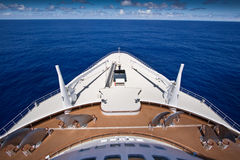 View over the bows of a cruise ship. View over the bows of a luxury cruise ship steaming in mid ocean under blue sunny sky, travel and vacation concept stock photos