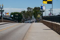 View over bridge to Balboa Island. There are no cars on bridge but traffic can be seen on the island. Nautical signal flags are flying on the bridge royalty free stock photography