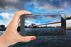 View over Brooklyn Bridge, New York with woman hand taking a picture with smartphone Royalty Free Stock Image