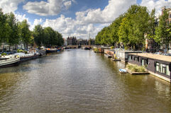 View over a canal in Amsterdam. A canal with typical houses and boats in Amsterdam, Netherlands Stock Image