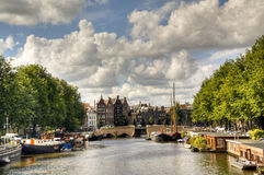 View over a canal in Amsterdam. A canal with typical houses and boats in Amsterdam, Netherlands Royalty Free Stock Images