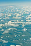 View over the clouds out of an airplane Stock Photos