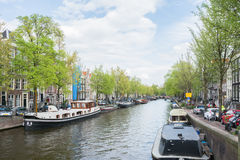 View over dutch canal with boats, houses facades and green trees. On a warm sunny day with blue sky and clouds in spring in Amsterdam, Netherlands Stock Image