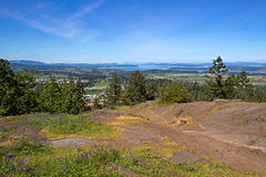 View Over Farms and Coast. View over the Saanich Peninsula on Vancouver Island on a sunny day. Rocky summit of Bear Hill in foreground. See farms, mountains Royalty Free Stock Image
