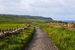 Small pedestrian path at Cliffs of Moher from Doolin, Ireland. View over the grassland and small pedestrian path at Cliffs of Moher from Doolin, Ireland royalty free stock photos
