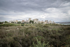View over grassland to cityscape and ruins with dramatic cloudscape in Tyre, Sour, Lebanon. View over grassland to cityscape and ruins with dark dramatic Royalty Free Stock Image