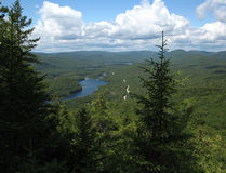 View over green mountain valley. And lakes through pine trees from Mont-Tremblant park in Quebec, Canada Stock Photos