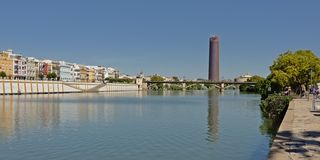 View over Guadalquivir river in the city of Seville. With Triana bridge and mofern Seville office tower reflecting in the water royalty free stock image