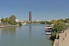 View over Guadalquivir river in the city of Seville. With Triana bridge and modern Seville office tower refecting in the water, and tourist boats moored on the stock images