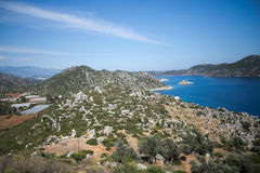 View over Kalekoy Simena bay in Uchagiz village. View of Kalekoy Simena bay in Uchagiz village of Antalya province of Turkey with ancient  lycian tombs in shape Royalty Free Stock Photography