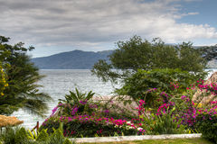 View over lake Apoyo near Granada, Nicaragua. View over lake Apoyo from a garden with beautiful flowers near Granada, Nicaragua Royalty Free Stock Image