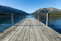 View over the lake towards mountains from grey pier Royalty Free Stock Images