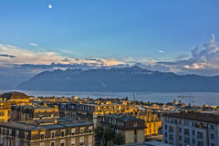 View over Lausanne roofs at sunset with lake Geneva and Alps. Picture taken in Lausanne, Switzerland on a summer evening Stock Photos