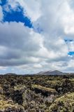 View over a lava field on Lanzarote with volcanoes in the background Royalty Free Stock Photos