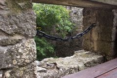 View over the loophole in the castle. View over the loophole protected chain in the castle. In the foreground is a wooden bench Stock Photos