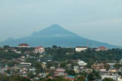View over Medan city with volcano in the background, Sulawesi, Indonesia. View over Medan city, the capital of North Sulawesi, on the island of Sulawesi Royalty Free Stock Photo