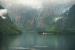 View over misty Lake Konigssee in Bavaria. View over misty Lake Konigssee with tiny St Bartholomae church in Berchtesgaden National Park, Bavaria, Germany Royalty Free Stock Photo