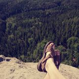 View over own legs to the word. Sandstone rock above valley. View over own legs to the word. rest on sandstone rock above valley. Long forest valley in hilly stock photos
