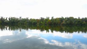View over the river. Surface water. Beautiful view over the water, calm river and behind it the green trees and forest, river reflected the pure blue sky and stock video