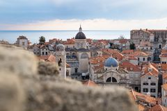 View over the roofs of old town Dubrovnik with church towers and ocean behind a stone wall, Croatia stock photography