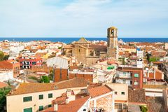 View over the roofs of old town Malgrat de Mar Spain from the hill with Mediterranean sea in the background. And the Cathedral of the Coast in the middle Royalty Free Stock Images