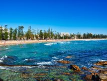 View Over Cabbage Tree Bay Rocks to Manly Beach, Sydney, Australia. View over sandstone rocks in Cabbage Tree Bay, with snorkelers swimming in water, to Manly stock photos
