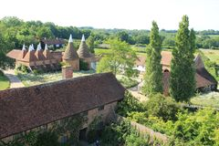 View over Sissinghurst Castle in Kent in England in the summer. View over Sissinghurst Castle and the oast house from the Tower in Kent in England in the stock photo