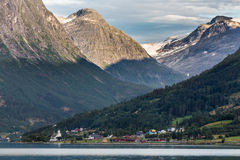 View over a small village in Norway. View over huge majestic mountains in contrast with a very small village in Norway Stock Image