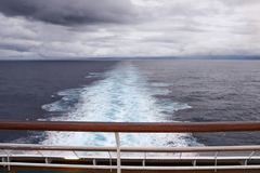 View over stern from upper deck of modern cruise ship. View over stern from upper deck of modern cruise ship showing wake extending into the distance on a grey Stock Images