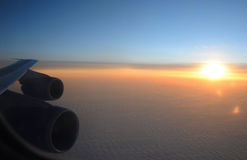 View over the sunset clouds from the plane. Sunset clouds from the plane with the detail of plane wing, fuselage and engines stock images