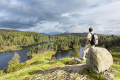View over Tarn Hows in English Lake District. Senior hiker looks over Tarn Hows in English Lake District Stock Images