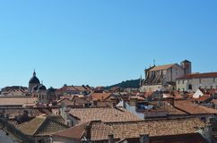 The roofline of Dubrovnik, against a blue sky. A view over the terracotta tiles covering the roofs of Dubrovnik. Some washing can be seen. The cathedral is to stock photography