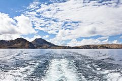 View over Titicaca Lake from a boat. A boats man, fishermen. Roa. D and boat trip to Isla del Sol, Island of the Sun. Located in Lake Titicaca in Bolivia. The Stock Photos