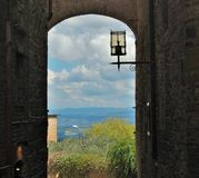 View over Tuscany landscape from a alley. View from a alley over the beautiful landscape of Tuscany Stock Image