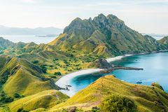 View of Padar Island in a cloudy evening with blue water surface and tourist boats royalty free stock image