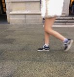 Woman`s legs walking on pavement royalty free stock image