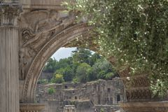 View of Palatine Hill ancient ruins through the Arch of Septimius Severus in Roman Forum Stock Photo