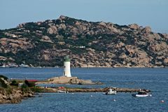 View of Palau lighthouse with boats moored in the blue sea of Sardinia Stock Photo