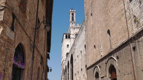 View of Palazzo dei consoli palace tower from a street in Gubbio, Umbria, Italy.  stock video footage