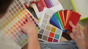 View of Palette in Female and Male Hands. Young Happy Family Choosing Colors for Their New Flat. stock video footage