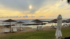 View on the parasols with deck chairs on beach near the sea. Silence and nobody around. Beautiful evening sea with yellow and orange sky. Bewitching nature stock video