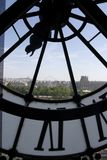 View of Paris through a clock at the Orsay Museum. View through a clock at the Orsay Museum. Looking at Le LOuvre museum, Sacre Coeur Basilica, and Tuileries Royalty Free Stock Photography